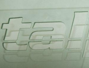 Vyřezávaný logotyp do plexiskla.
